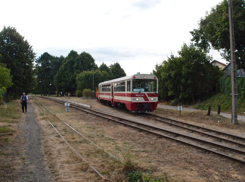 Vlak tažený historickým úzkorozchodným motorovým vozem MBxd2 odjížděje ze stanice Stegna se blíží k výhybce, kde se napojí na trať souběžnou s pobřežím.